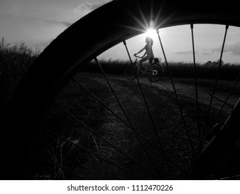 Silhouette of a girl enjoying a bike ride at sunset time. High contrast black and white photograph.