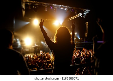Silhouette of Girl enjoying the music show, stage light