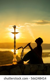 silhouette of a girl exhales smoke hookah at sunset background