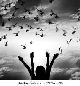 Silhouette of girl and flying dove on sky background, freedom and peace concept black and white