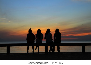 Silhouette of girl group in the morning at the beach waiting for the sunrise.