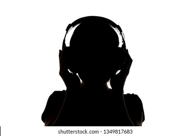 Silhouette of girl in headphones listening music in headphones isolated on white