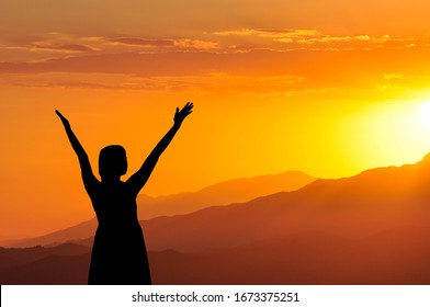 The silhouette of a girl with her hands raised in the air turned towards the sunset in the mountains