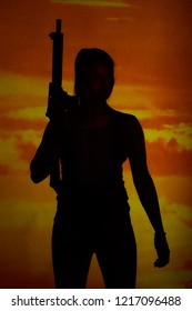 Silhouette of girl holding carbine in sunset