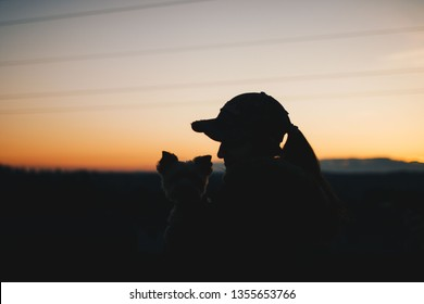 Silhouette of girl holding dog at sunset