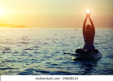 Silhouette of a girl holding sun in the hands on sup yoga meditation, harmony with the nature in yoga meditation during beautiful dawn