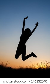Silhouette of girl jumping in field