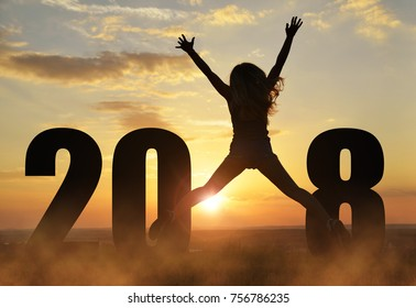 Silhouette of a girl jumps up while celebrating New Year 2018.