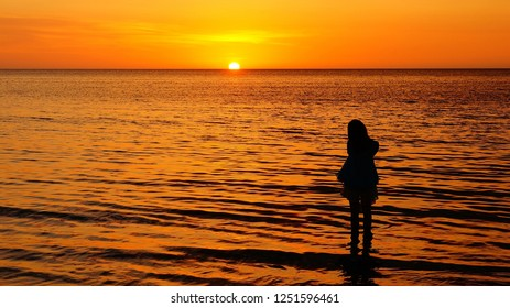 Silhouette of a girl looking at sunset on the horizon with her feet dipped in the soft sea water at her blissful moment. First Beach Tanjung Aru, Kota Kinabalu, Malaysia