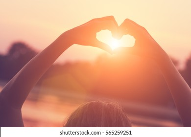 Silhouette of a girl making a heart-shape in nature.