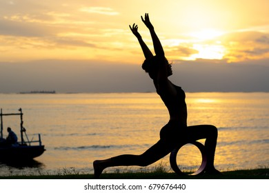 silhouette of a girl Meditate by practicing yoga at the seafront at sunset time.