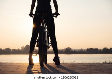 Silhouette of a girl near sea on the bike. Sport and active life concept