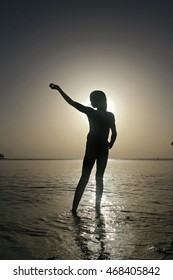 silhouette of a girl in ocean with sunset background