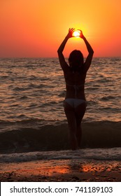 Silhouette of a girl on the beach with the sun in her hands at sunset