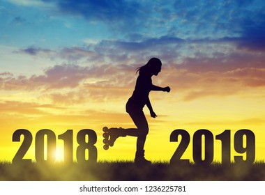 Silhouette the girl on roller skates at sunset. Forward to the New Year 2019.