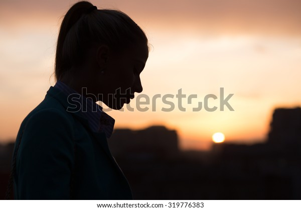 silhouette of a girl on the roof at sunset in the city