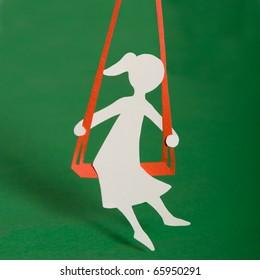 Silhouette of girl on swing.