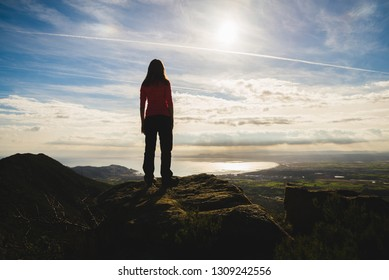 Silhouette of a girl on top of a cliff admiring the beautiful landscape view, in the middle of nature, in Catalonia, Spain
