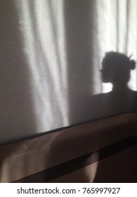 Silhouette of the girl on the wall and furniture. The shadow of the girl on the wall and the back of the sofa in soft colors.