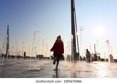 silhouette of girl playing outside in street fountains in winter wearing pink coat