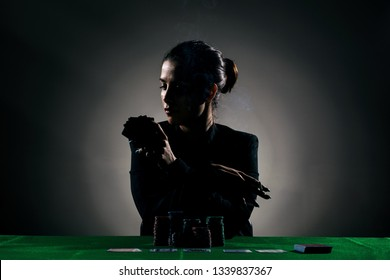 silhouette girl playing poker with lot of chips and holding a cigar