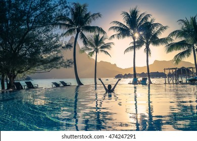 Silhouette of a girl in the pool. Sunset in Bora Bora , French Polynesia . Mount Otemanu in the background. Retro style color tones.