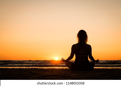 Silhouette of a girl practicing yoga on the beach at sunset