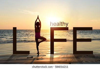 Silhouette of A girl practicing Yoga vrikshasana tree pose on tropical beach with sunset sky background, watching the sunset, standing as a part of the wording concept for healthy life.