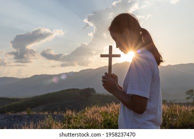 Silhouette of girl praying and holding christian cross for worshipping God at sunset background. Christian, Christianity, Religion copy space background.