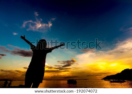 silhouette of girl raising her hands to the sky at dusk