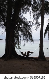 Silhouette of a girl reading a book in the hammock at the beach