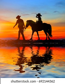 silhouette, girl riding a horse on the beach and water reflection.