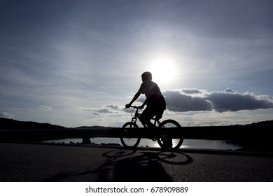 Silhouette of a girl riding on a mountain bike on a road running along a reservior shore