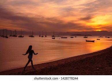 The silhouette of a girl running in the beach at the sunset in Santo Antonio de Lisboa, Florianopolis, Santa Catarina, Brazil