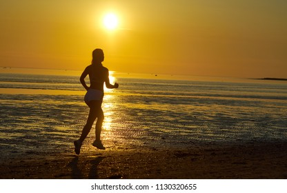 silhouette of girl running by the sea on the beach at sunrise,Sunset black beach background with sun. Woman fitness jogging sport activity on summer