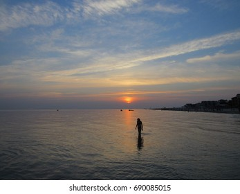 Silhouette of a girl in the sea at sunset time