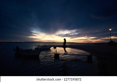 Silhouette of girl in short dress standing on narrow wooden bridge at small motor boats anchored at shore in sea inlet calm shallow water chained to pier on bright cloudy sky at sunset background.