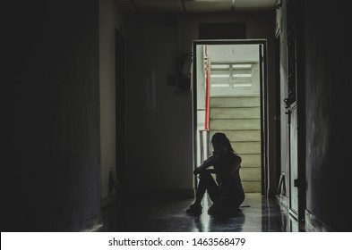 Silhouette of girl sitting alone in the dark,Sad and Serious women sitting hug his knee alone of old condo, Domestic violence, family problems,The concept of depression and suicide with copy space