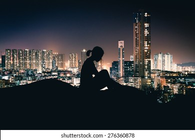 Silhouette of Girl Sitting in front of City Light