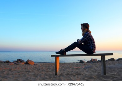 Silhouette of a girl sitting on the bench.Sea shore.
