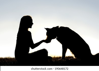 A silhouette of a girl sitting outside in the grass with her pet German Shepherd Mix Dog, feeding him treats during training, in front of a sunsetting sky.