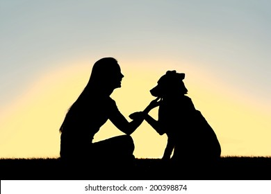 A silhouette of a girl sitting outside, training and playing with her German Shepherd dog, as he shakes her hand isolated in front of a sunset in the sky.
