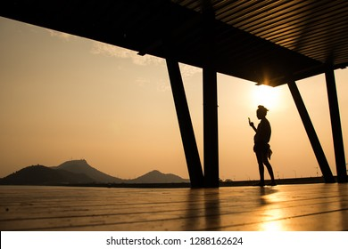 The silhouette of a girl standing on the balcony In the light of the sun that is about to fall, she uses the phone to shoot the view. She looks happy