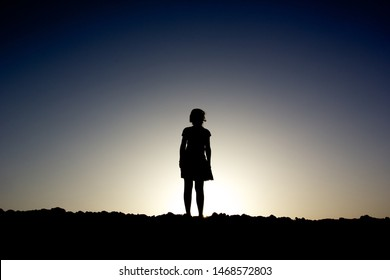 Silhouette of a girl standing on a hill