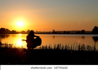 silhouette of a girl at sunrise playing the guitar by the river