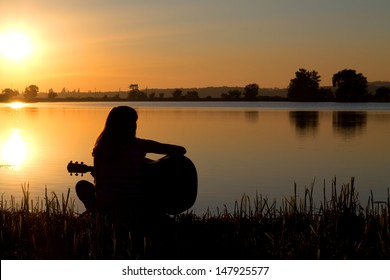 silhouette of a girl at sunset playing the guitar by the river
