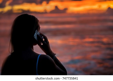 silhouette of a girl at sunset, speaks by mobile phone