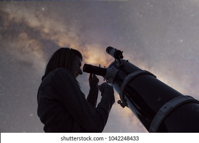 Silhouette of a girl and telescope with de-focused Milky Way stars. My astronomy work.