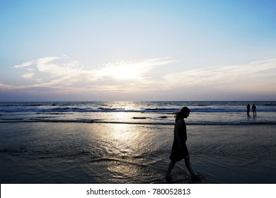 silhouette of girl, walking on the beach in the sunset