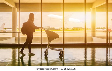 silhouette of a girl walkingsilhouette of a girl walking at the airport glass window, girl tourist hold bag and waiting near luggage in hall airplane departure. Travel Concept.